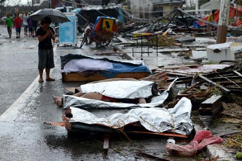 ... và những xác chết nằm la liệt khắp mọi nơi, mọi con đường, lẫn giữa những đống đổ nát. Trong hình, một phụ nữ đang chắp tay cầu khấn trước thi thể của người chồng trên đường phố.Tất cả mạng lưới liên lạc, ngoại trừ điện thoại vệ tinh, đều bị cắt đứt, thực phẩm, nước uống và thuốc men đều hiếm hoi.