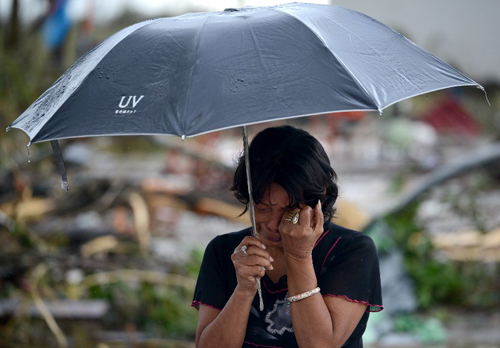 [Caption]A woman mourns in front of her husband's dead body in a street of Tacloban, eastern island of Leyte on November 10, 2013.