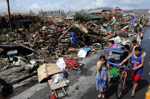 [Caption]esidents walk past destroyed houses and dead bodies littered along a road in Tacloban, on the eastern island of Leyte on November 10, 2013 after Super Typhoon Haiyan swept over the Philippines